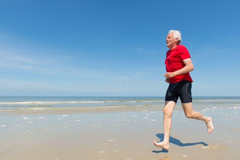Старший человек бежать на пляже стоковое изображение rf