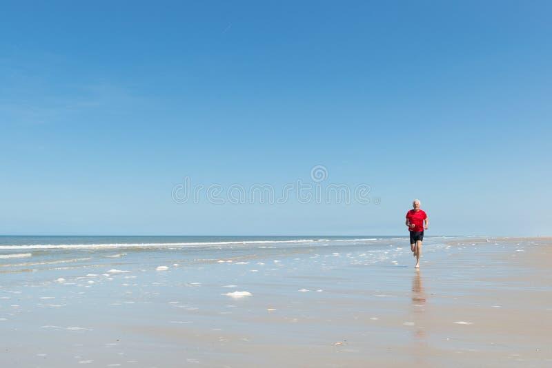Старший человек бежать на пляже стоковое фото rf
