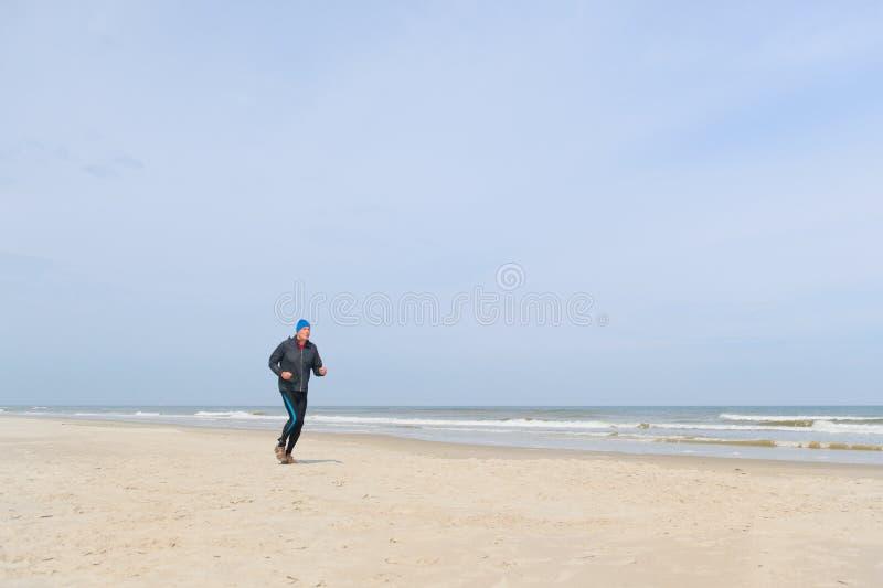 Старший человек бежать на пляже стоковое изображение