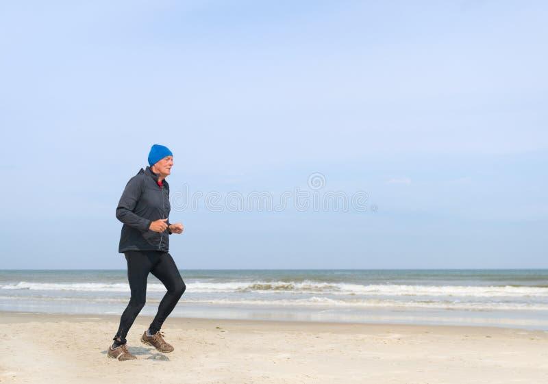 Старший человек бежать на пляже стоковые изображения rf
