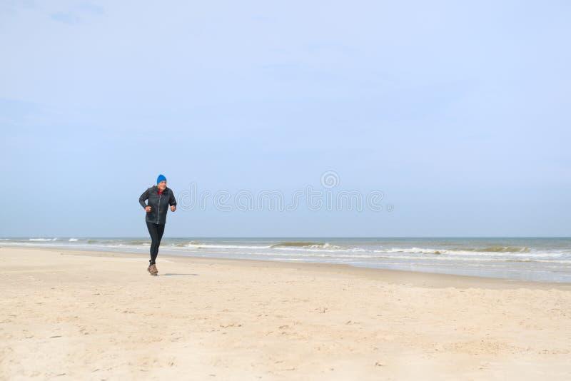 Старший человек бежать на пляже стоковая фотография rf