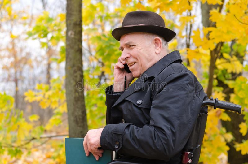 Старший человек в кресло-коляске беседуя на его черни стоковая фотография