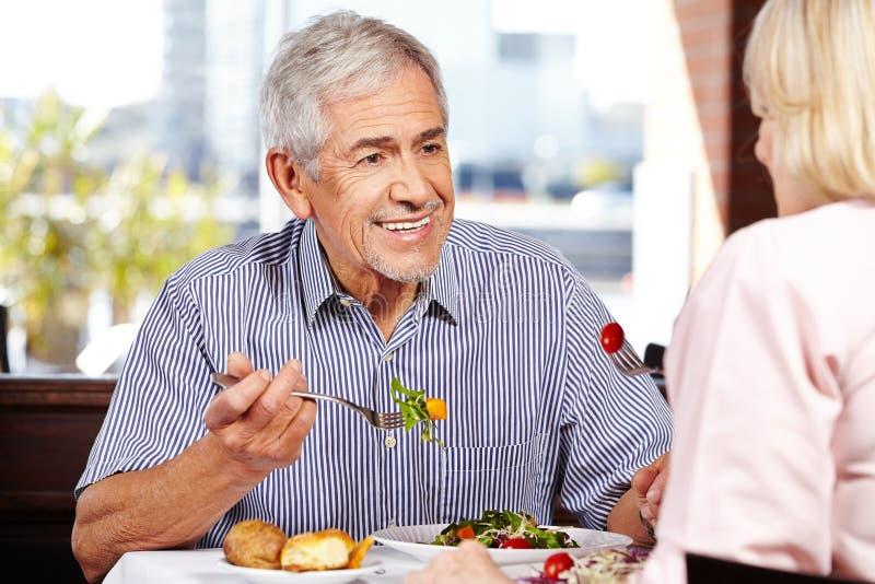 Старший человек говоря к женщине пока стоковые изображения rf