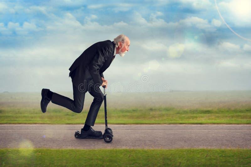 Старший человек ехать самокат стоковые изображения