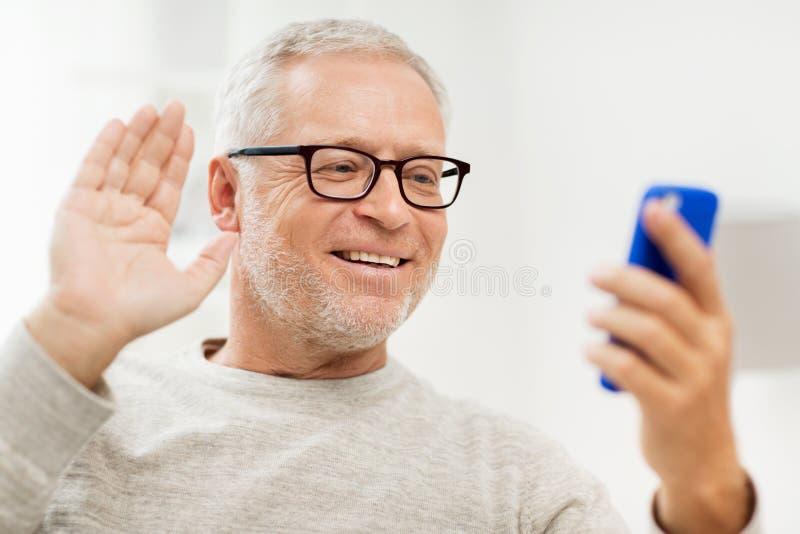 Старший человек имея видео- звонок на smartphone дома стоковое фото rf