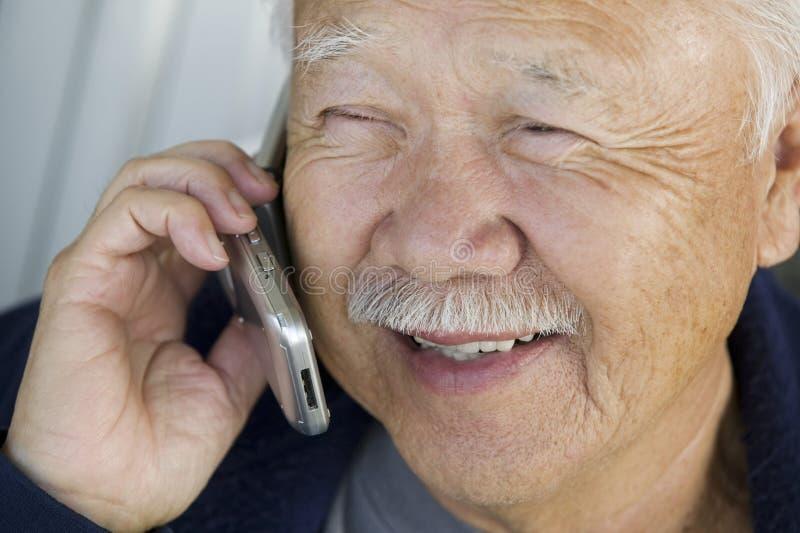 Старший человек используя мобильный телефон стоковая фотография rf