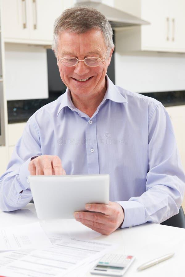 Старший человек используя таблетку цифров для того чтобы проверить личные финансы стоковое фото