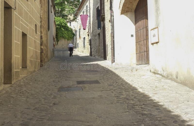 Старший человек идя в средневековую улицу в Trujillo стоковые изображения