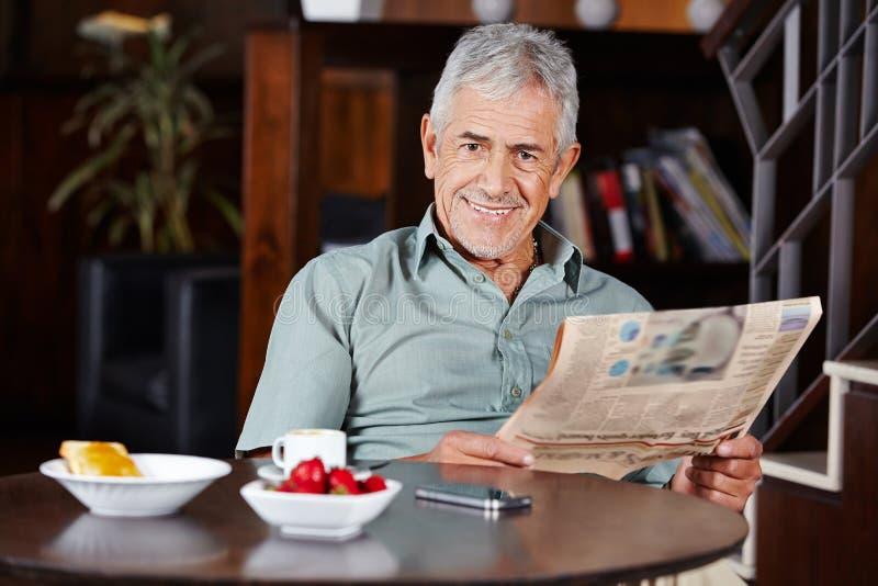 Старший человек на завтраке с газетой стоковое изображение