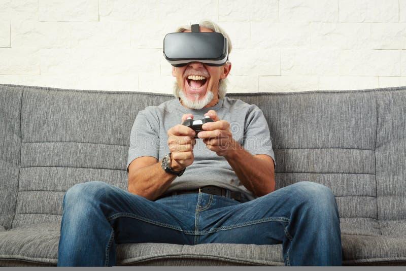 Старший человек на кресле, играя игру Vr стоковая фотография rf