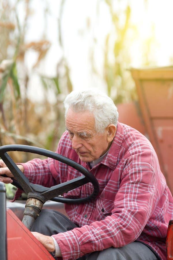 Старший человек на тракторе стоковое фото rf