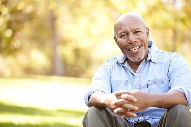 Старший человек ослабляя в ландшафте осени стоковые фотографии rf