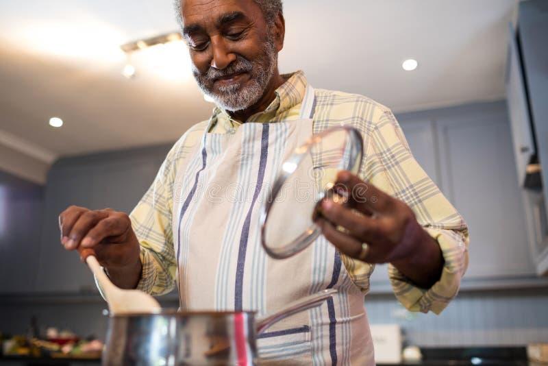 Старший человек подготавливая еду дома стоковое фото rf