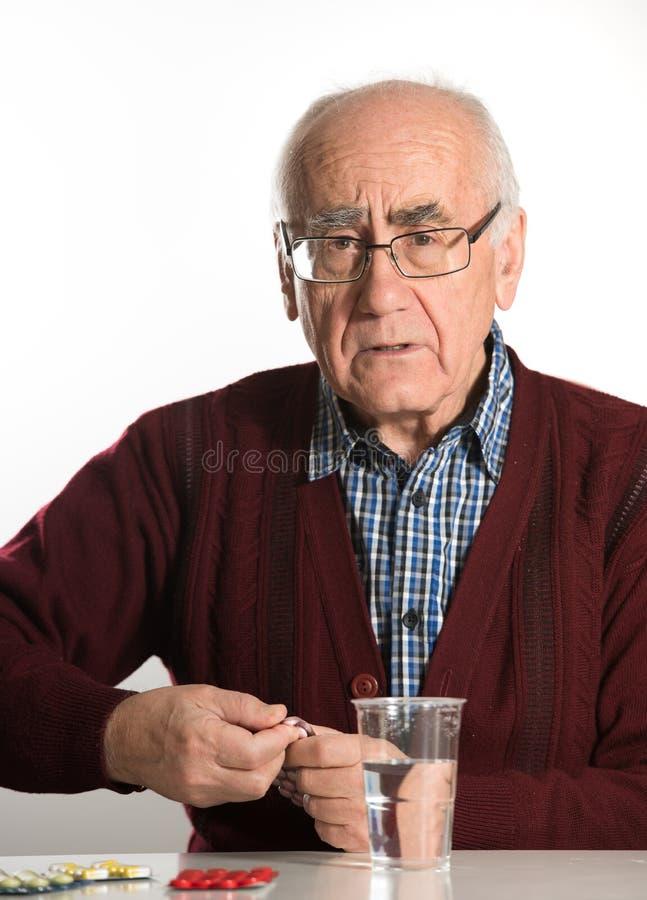 Старший человек принимая пилюльки стоковые изображения rf