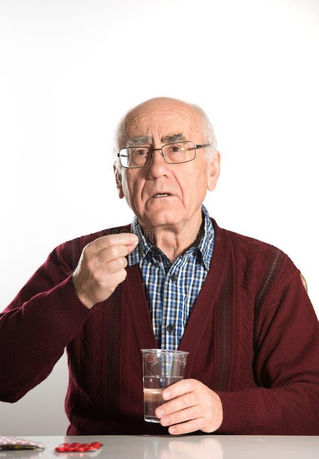 Старший человек принимая пилюльки стоковые изображения
