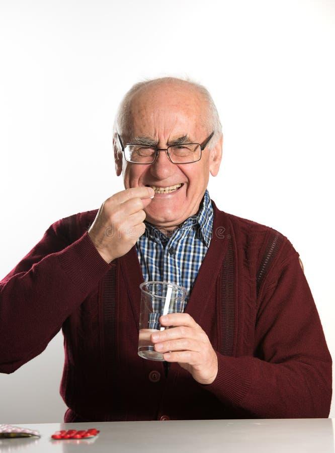 Старший человек принимая пилюльки стоковые фото