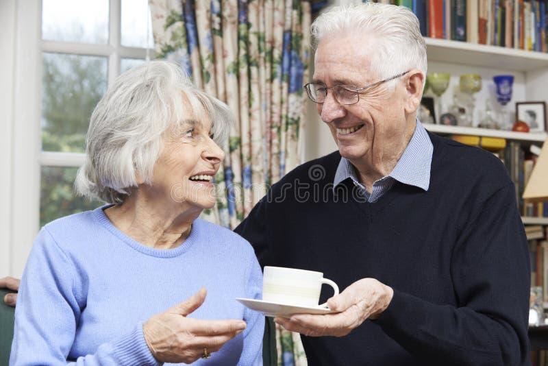 Старший человек принося чашку чаю жены стоковое изображение rf