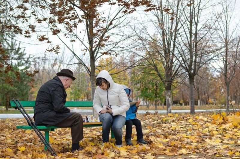 Старший человек планируя его следующее движение шахмат сидя в banch парка стоковые фотографии rf