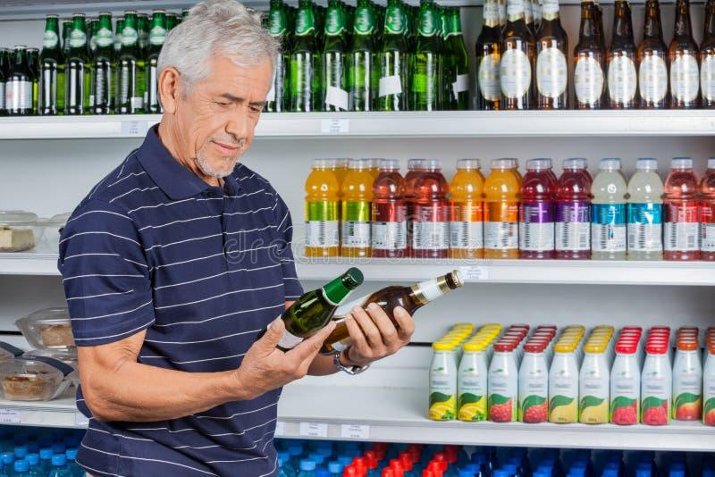 Старший человек сравнивая пивные бутылки стоковая фотография