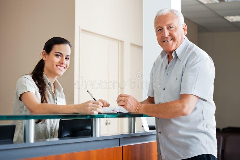 Старший человек стоя на приеме больницы стоковые фото