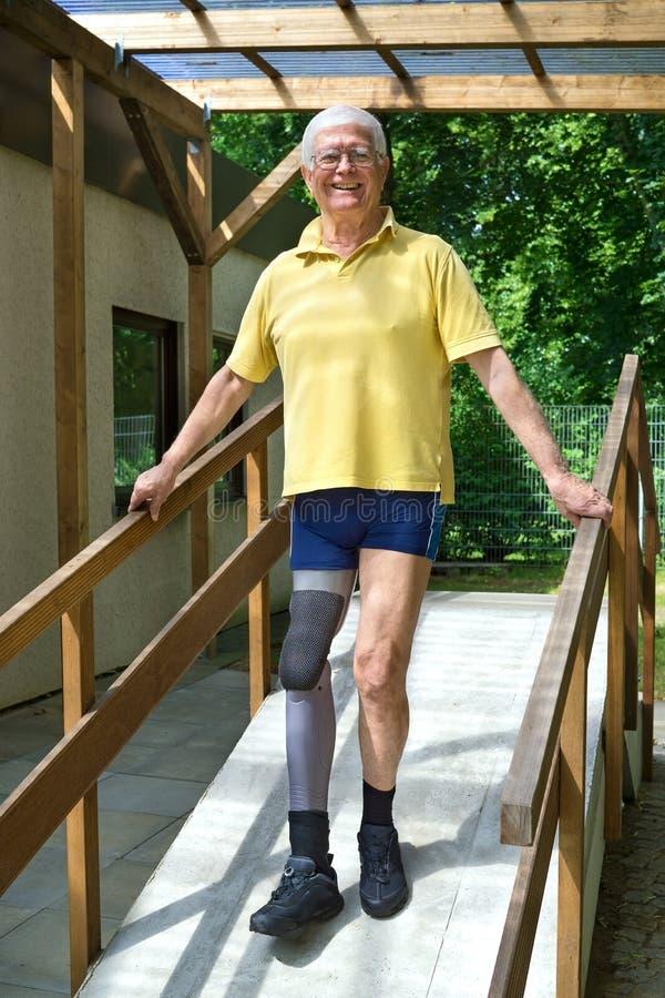 Старший человек с ампутированной конечностью ноги идя вниз с пандуса для тренировки стоковая фотография