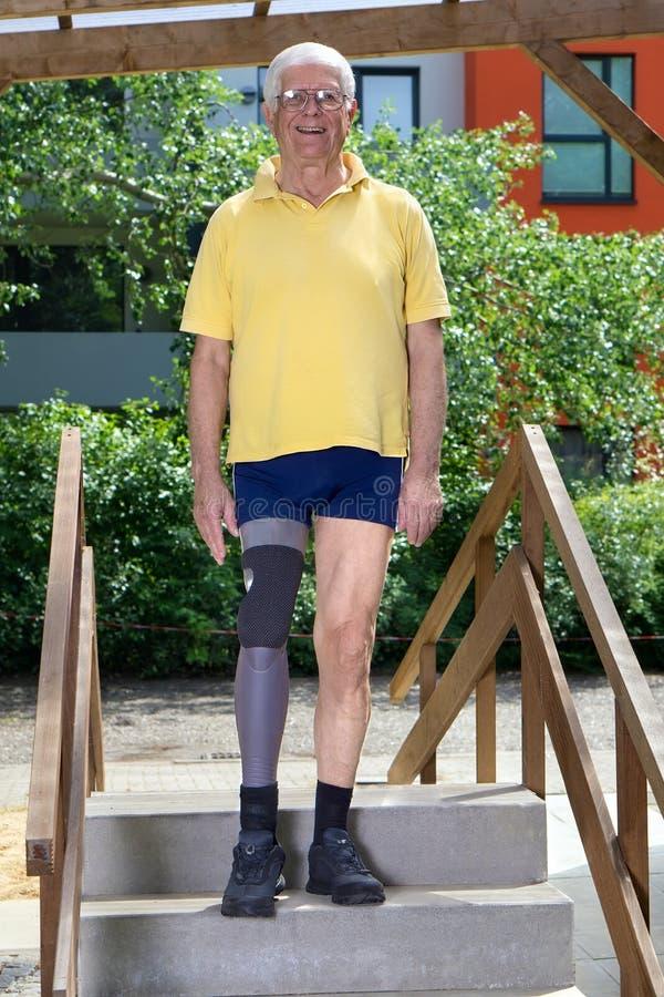 Старший человек с ампутированной конечностью ноги стоя на лестнице курса подготовки для практиковать стоковое изображение rf