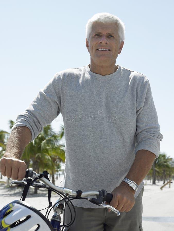 Старший человек с велосипедом на тропическом пляже стоковые фотографии rf