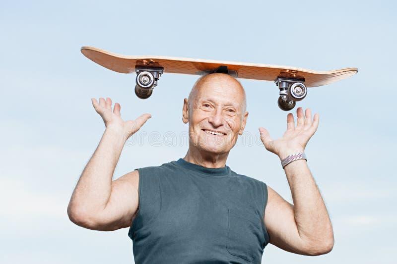 Старший человек с скейтбордом на его голове стоковое фото rf