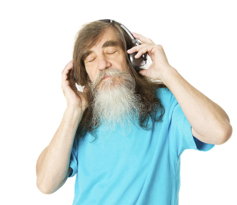 Старший человек слушая к музыке в наушниках Старик с бородой стоковая фотография rf