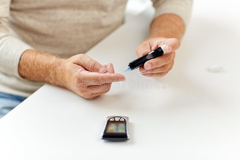 Старший человек с glucometer проверяя уровень сахара в крови стоковые фотографии rf