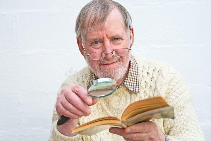 старший чтения увеличителя помощи стоковая фотография
