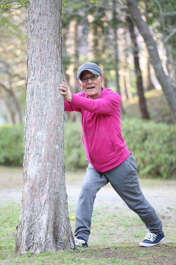 Старший японский человек нося розовый parka делая простирание икры деревом стоковая фотография