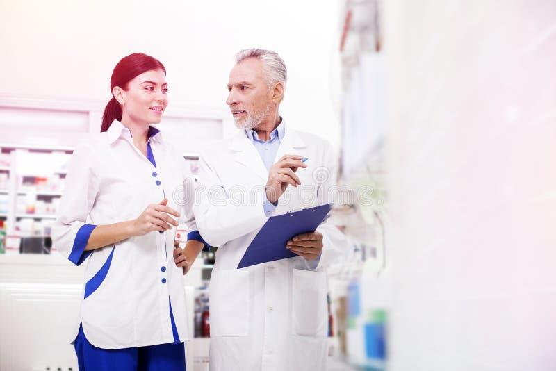 Старший druggist спрашивая товарищу по работе о поставке новых лекарств стоковые фото