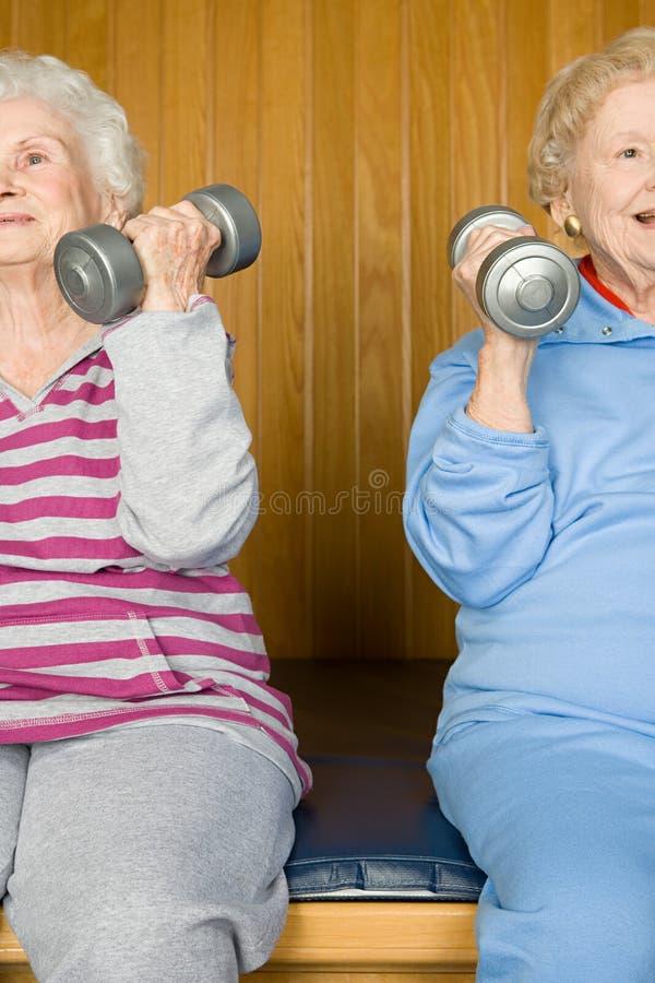2 старших женщины поднимая гантели стоковые фото