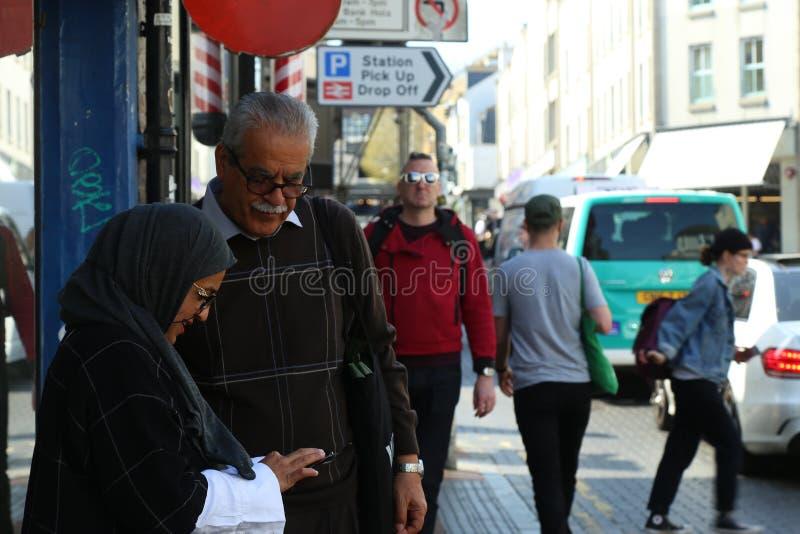 2 старших мусульманских люд на стороне дороги смотря телефон Брайтон, Великобритания стоковое фото rf