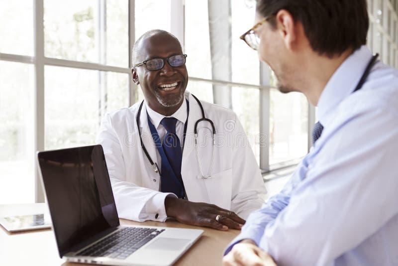 2 старших работника здравоохранения в смеяться над консультации стоковые фотографии rf