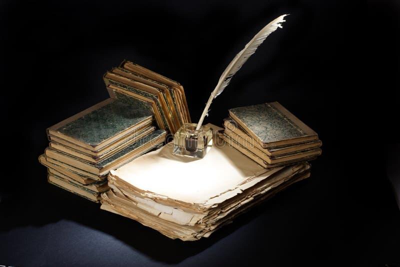 Старые авторучка, книги и чернильница на черной предпосылке стоковые фотографии rf