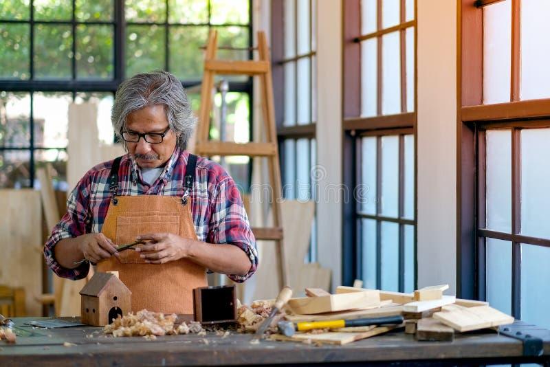 Старые азиатские крумциркули пользы мастера для помогать работать с изделием из древесины в комнате во время времени дня стоковые изображения