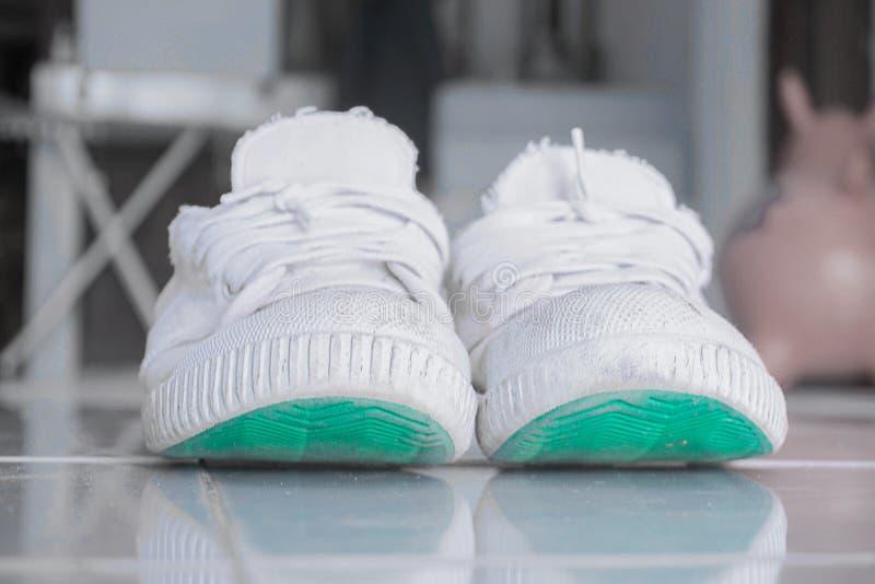 Старые белые ботинки используемые для того чтобы сыграть спорт стоковые изображения