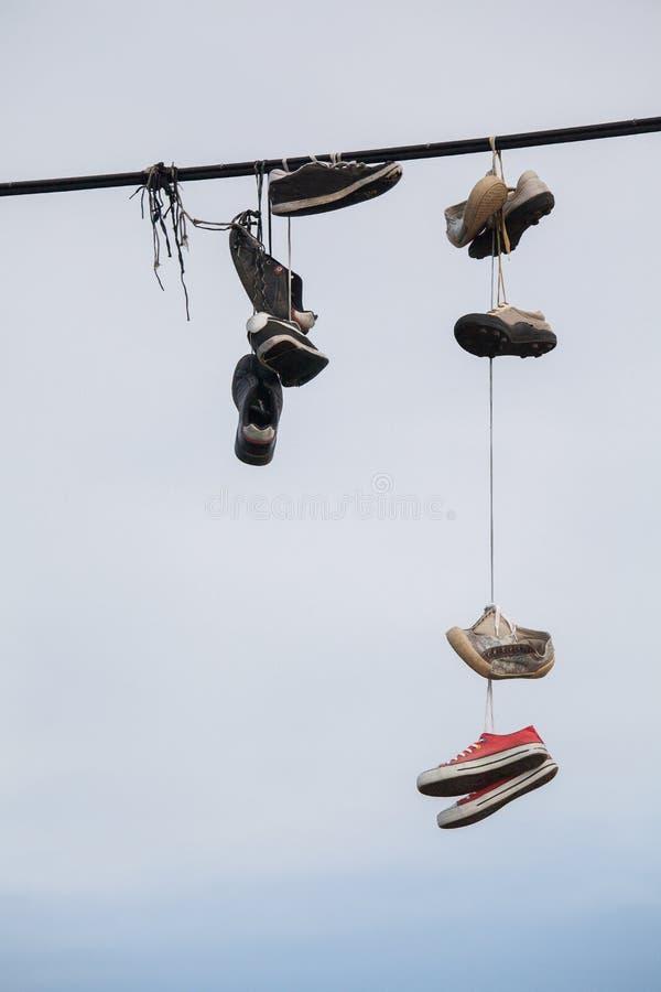 Старые ботинки вися на проводе - изменении жизни стоковая фотография