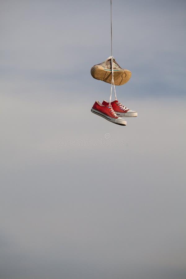 Старые ботинки вися на проводе - изменении жизни стоковое изображение rf