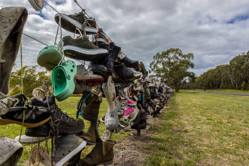 Старые ботинки на загородке рядом с дорогой в Австралии турист положил их старые ботинки на загородку стоковые фото