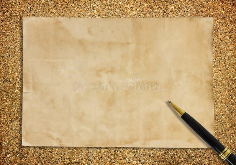 Старые бумага и ручка на песке для предпосылки текстуры стоковые фото