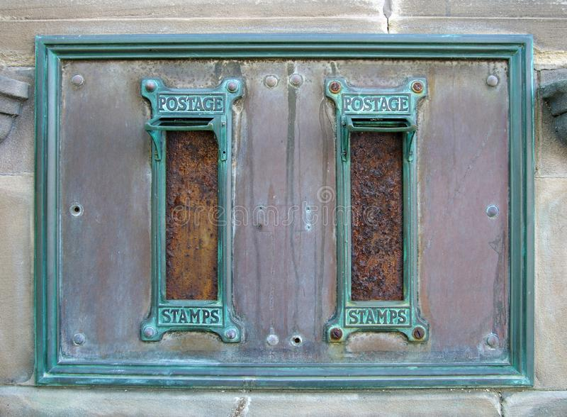 Старые великобританские почтовые коробки почты с заржаветыми слотами письма и богато украшенные зеленые медные рамки с печатями п стоковые фото