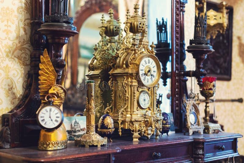 Старые винтажные античные бронзовые часы и утварь на деревянной полке, концепции антиквариатов стоковое фото