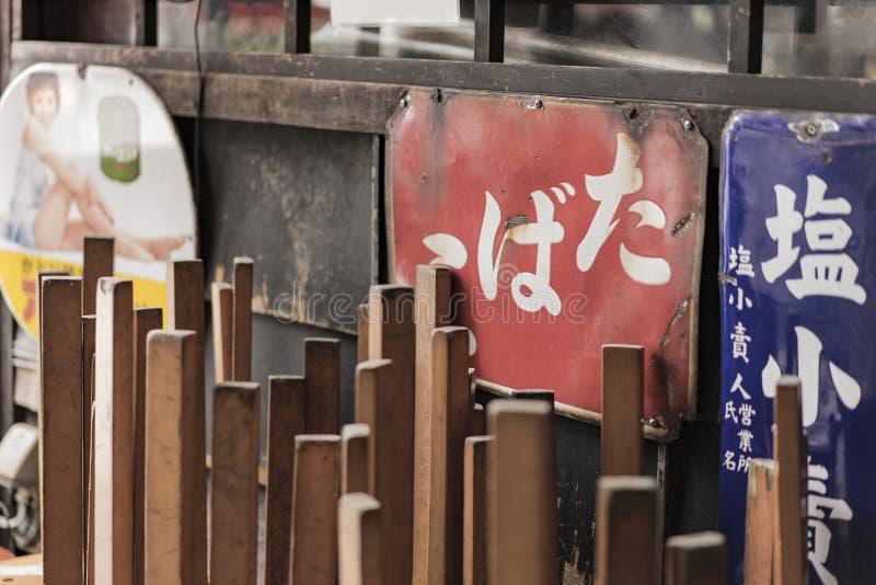 Старые винтажные ретро японские знаки металла и красный фонарик рисовой бумаги где пишут Oshokujidokoro которое значит еду на под стоковое фото