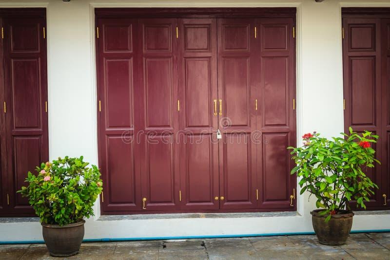 Старые старые выдержанные двойные красные двери в тайском виске стоковое фото rf