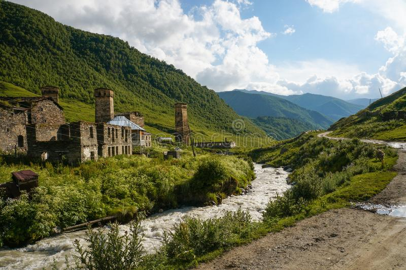 старые выдержанные здания против малого реки текут против холмов, Ushguli, стоковое изображение rf