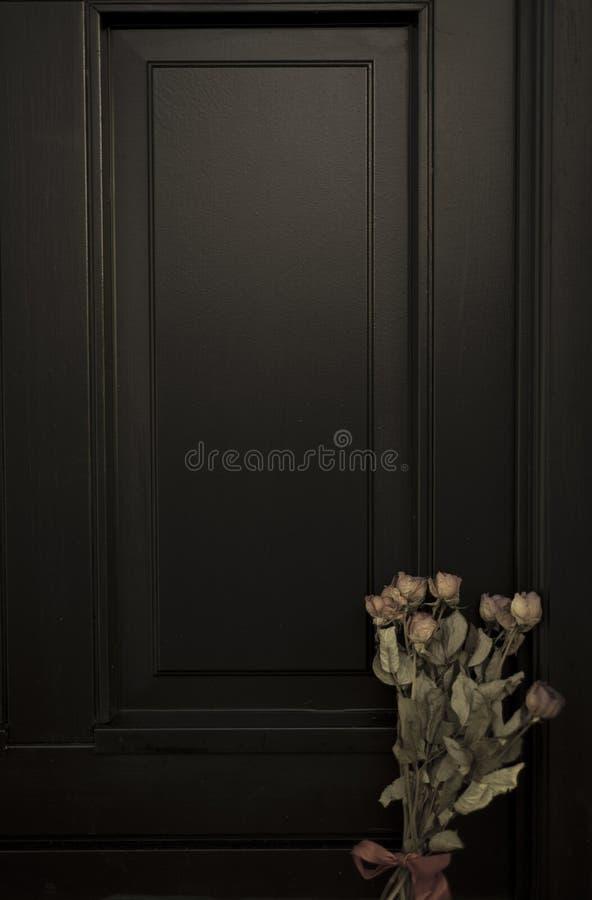 Старые вянуть розы дверью стоковая фотография