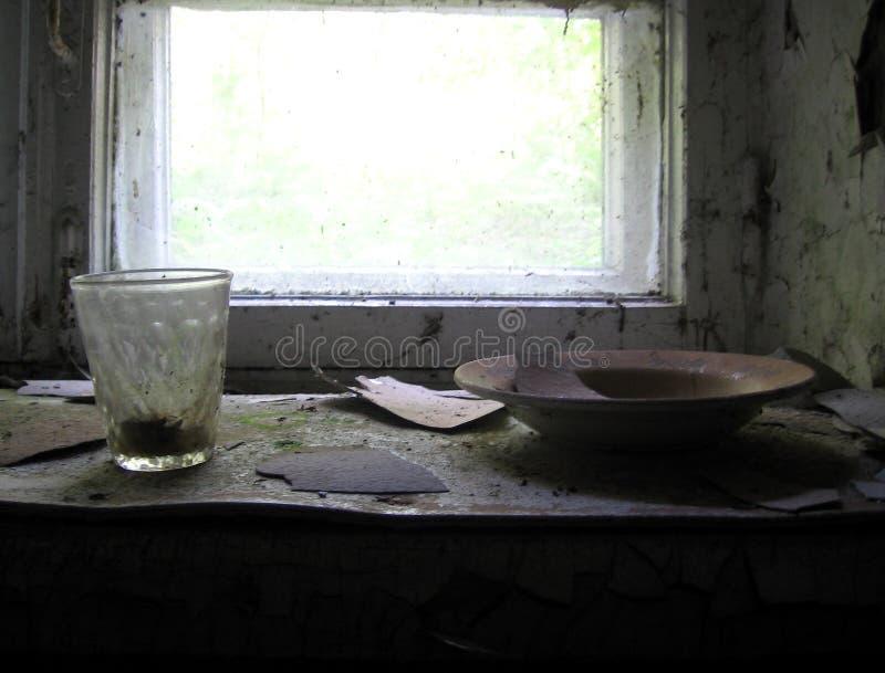 старые грязные блюда стоя на windowsill сломленного окна стоковая фотография